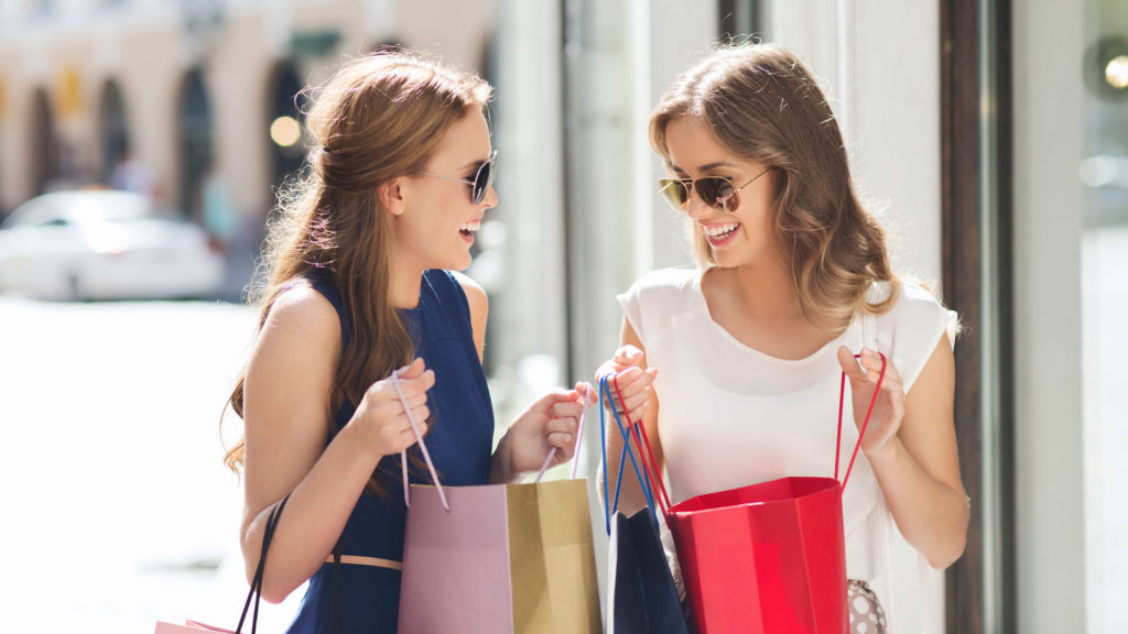 happy-women-with-shopping-bags-in-city-000075277079_medium